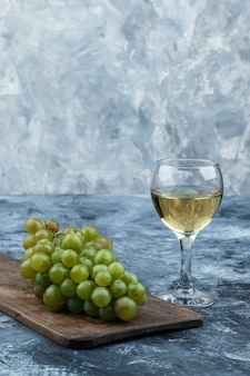 Ensemble de verre de vin et de raisins blancs sur une planche à découper sur un fond de marbre bleu foncé et clair. fermer.
