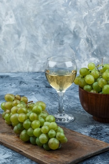 Ensemble de verre de vin, raisins sur une planche à découper et raisins blancs dans un bol sur un fond de marbre bleu foncé et clair. fermer.