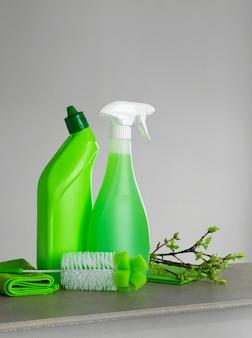 Ensemble vert pour le nettoyage de printemps et quelques brindilles avec de jeunes feuilles de printemps.
