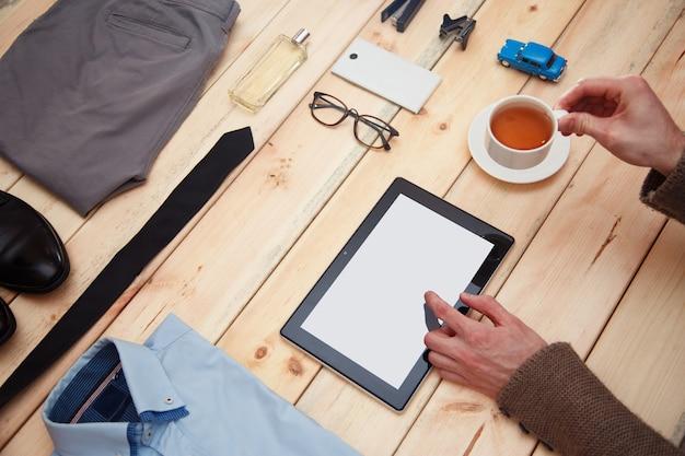 Ensemble de vêtements et accessoires pour homme sur une surface en bois.