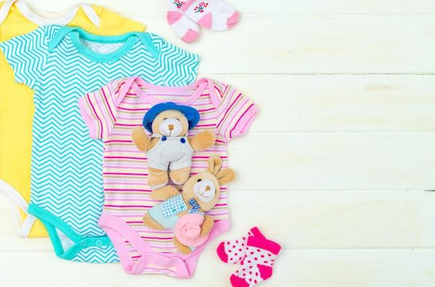 Ensemble de vêtements et d'articles pour un nouveau-né placé sur une planche en bois blanche.