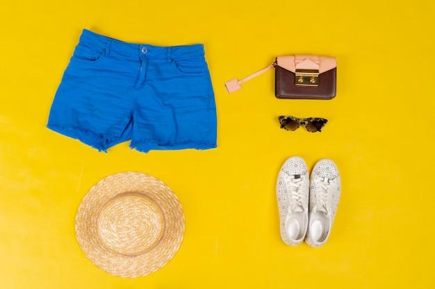 Ensemble de vêtements féminins et accessoires sur fond jaune vif