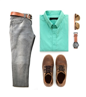 Ensemble de vêtements pour hommes avec bottes marron, montre, jeans, lunettes de soleil et chemise verte isolé sur fond blanc, vue de dessus