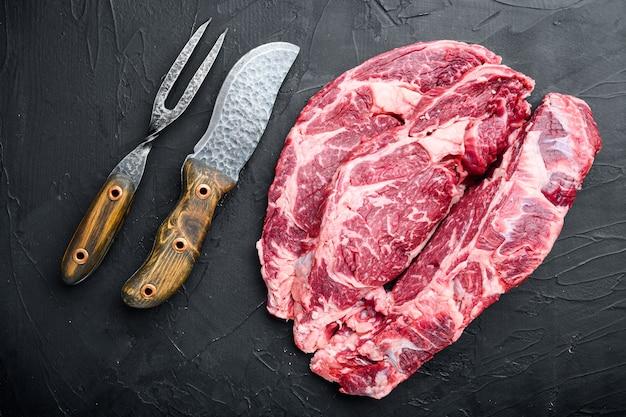 Ensemble de viande marbrée crue, faux-filet coupé, sur pierre noire, vue de dessus à plat