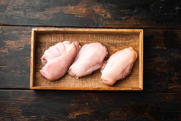 Ensemble de viande de poulet fraîche, dans une boîte en bois, sur une vieille table en bois foncé