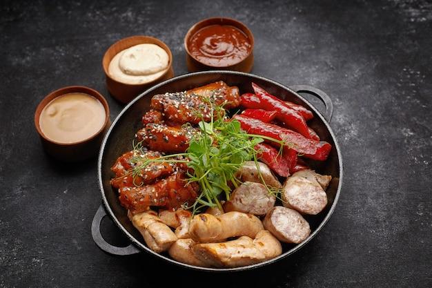 Ensemble de viande, saucisse, côtes levées, ailes grillées et trois sauces sur fond noir