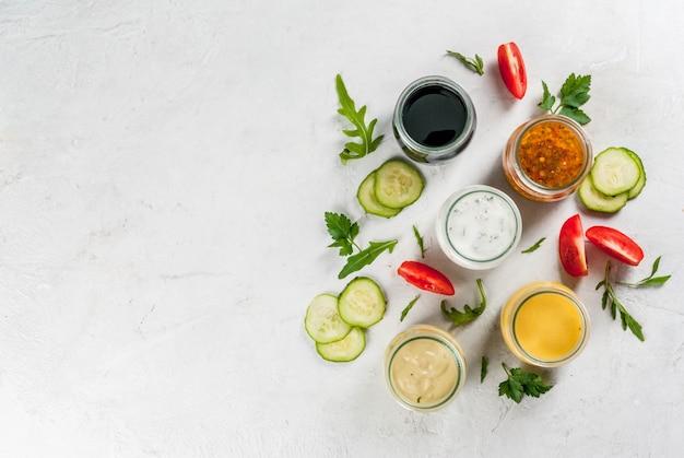 Ensemble de vinaigrettes pour salade: sauce vinaigrette, moutarde, mayonnaise ou ranch, balsamique ou soja, basilic au yaourt. table en béton blanc foncé, avec verdure, légumes pour salade. copier la vue de dessus de l'espace