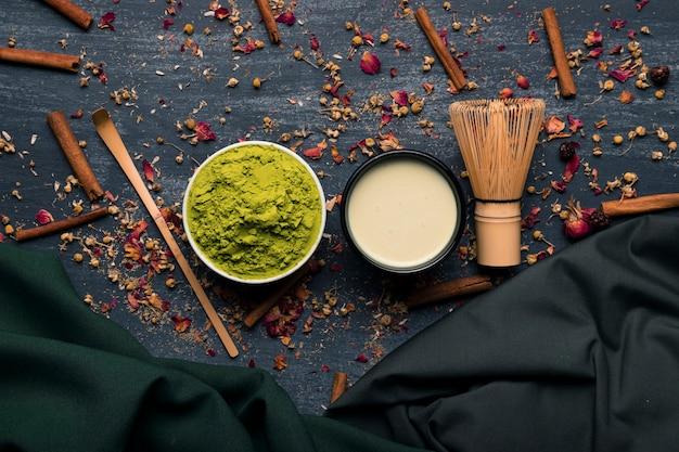 Ensemble vue de dessus de thé matcha asiatique avec des bâtons de cannelle