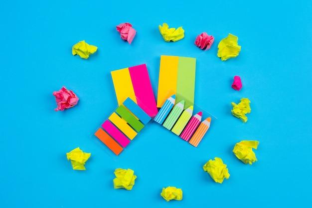 Des ensembles d'autocollants de couleurs vives situés sur un mur bleu situé au centre, à côté desquels se trouvent des autocollants en forme de rayures et de crayons au centre desquels des autocollants froissés sont disposés.