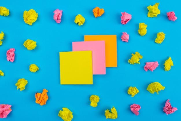 Des ensembles d'autocollants jaunes, roses et orange superposés situés au centre, entourés d'autocollants froissés de différentes couleurs. fermer. définir pour les notes.