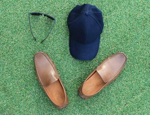 Ensembles de chapeau, lunettes de soleil et chaussures sur l'herbe verte