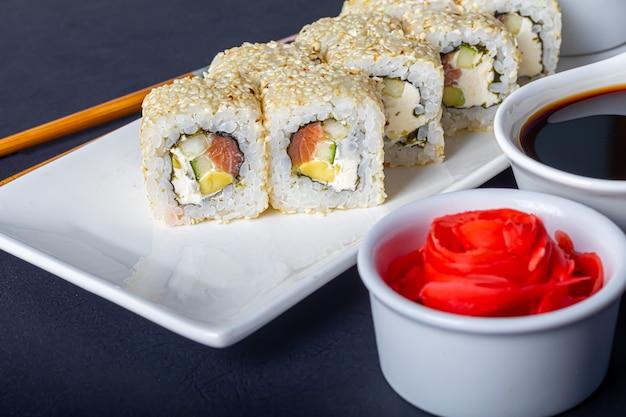 Ensembles de sushi uramaki, californie, philadelphie, sur une assiette blanche. gingembre et wasabi à proximité.