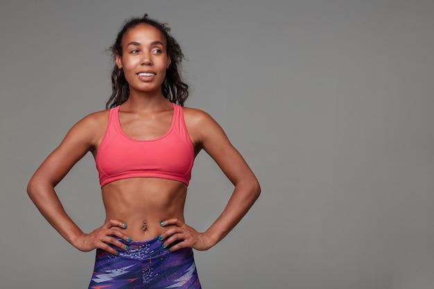 Enthousiaste athlétique jeune femme brune frisée à la peau foncée étant en bonne forme physique en position debout. concept de sport et de mode de vie sain