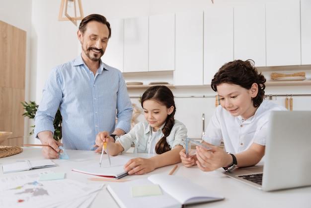 Enthousiaste beau garçon tenant un carré tandis que sa sœur à l'aide d'une paire de boussoles et leur agréable jeune père les regarde avec un sourire affectueux