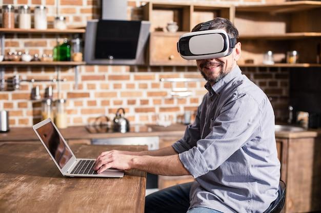 Enthousiaste bel homme d'affaires portant vr deviner tout en travaillant sur l'ordinateur portable