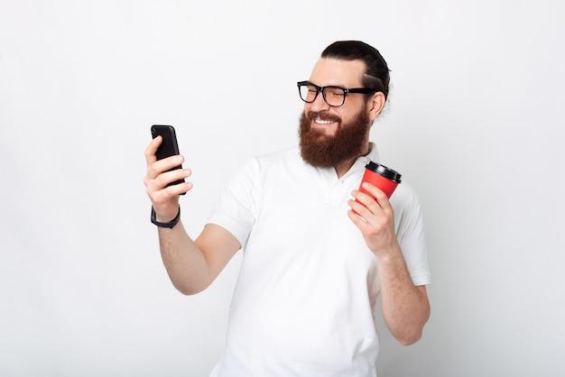 Enthousiaste bel homme barbu à l'aide de smartphone et tenant une tasse de café sur fond blanc