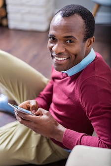 Enthousiaste bel homme souriant et regardant directement tout en utilisant son appareil mobile