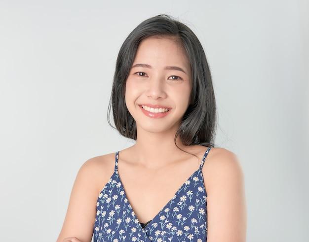 Enthousiaste belle femme asiatique stand et les bras croisés sur fond gris.