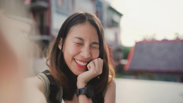 Enthousiaste belle jeune femme asiatique blogueur backpacker à l'aide de smartphone prenant selfie