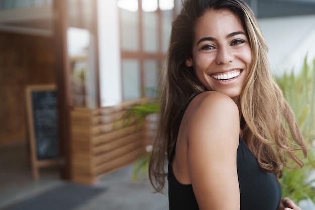 Enthousiaste belle jeune femme bronzée se pencher sur la terrasse et regarder joyeusement