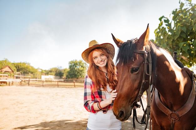 Enthousiaste belle jeune femme cowgirl debout avec son cheval dans le village