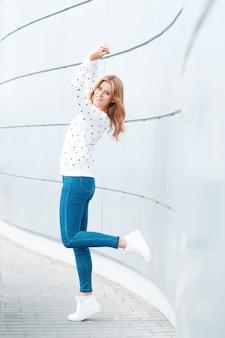 Enthousiaste belle jeune femme positive dans des vêtements à la mode s'amuser sur une chaude journée de printemps à l'intérieur près du mur moderne