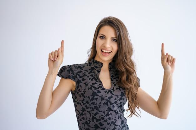 Enthousiaste belle jeune fille brune aux cheveux longs dans une robe pose sur fond blanc, lève les doigts