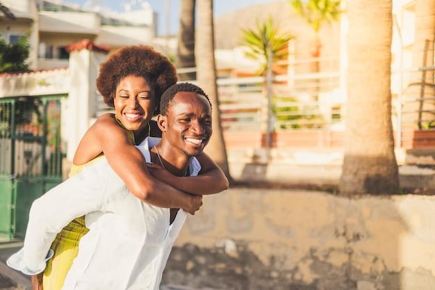 Enthousiaste et bonheur pour les couples de race afro noire jouent et profitent de la journée ensoleillée. la fille reste sur le dos du garçon qui la porte en riant tous les deux. beau mode de vie enojying millénaire des jeunes