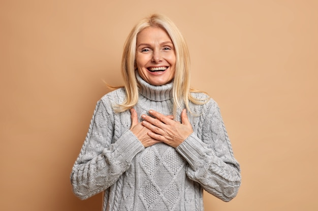Enthousiaste bonne femme d'âge moyen garde les mains appuyées sur la poitrine sourit largement et exprime des émotions positives vêtue d'un pull d'hiver heureux d'entendre le compliment.