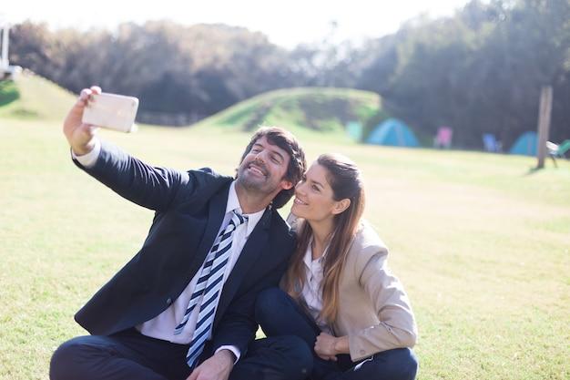 Enthousiaste collègues prenant selfie avec un téléphone mobile