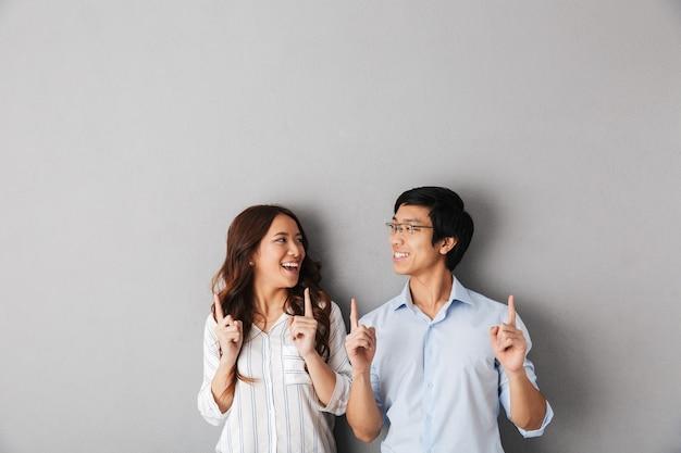 Enthousiaste couple d'affaires asiatiques debout isolé, pointant les doigts vers le haut