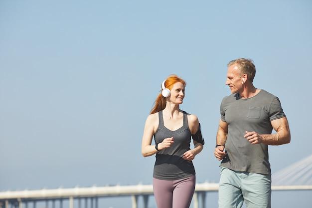 Enthousiaste couple d'âge mûr bavardant en faisant du jogging ensemble sur la rue de la ville, concept de mode de vie sain