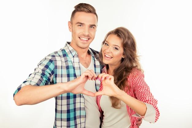 Enthousiaste couple amoureux s'embrassant en faisant un geste de coeur