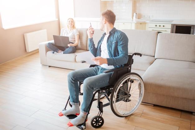 Enthousiaste couple dans la chambre ensemble. jeune homme avec inclusivité s'asseoir sur un fauteuil roulant et regarder en arrière sur la femme.
