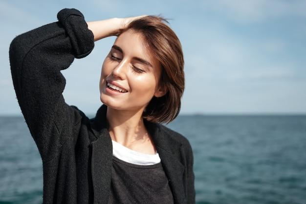 Enthousiaste détendue jeune femme debout et souriant