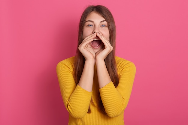 Enthousiaste drôle jeune femme portant chandail jaune criant avec le geste de la main près de la bouche isolée sur mur rose, dame aux cheveux longs