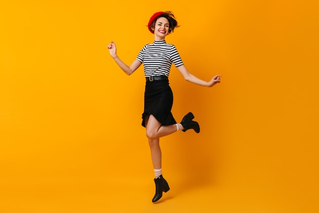 Enthousiaste élégante femme française danse sur mur jaune