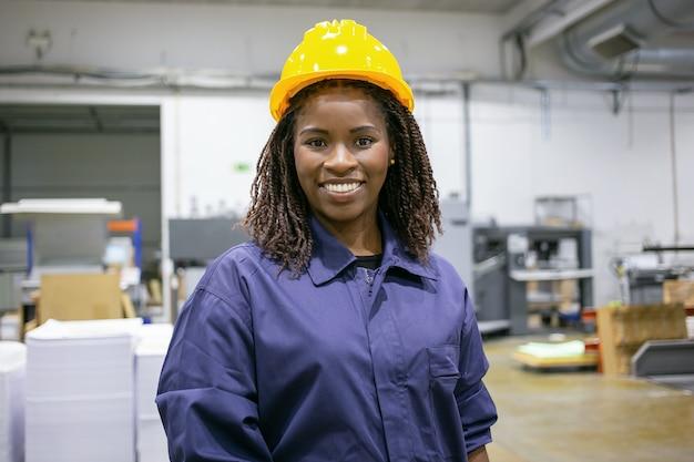 Enthousiaste employé d'usine afro-américaine en casque et globalement debout sur le sol de l'usine, regardant à l'avant et souriant