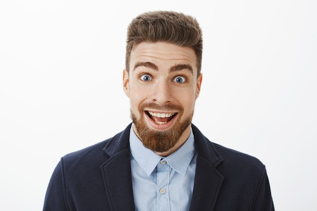 Enthousiaste, excité et surpris, bel homme heureux avec une barbe et des yeux bleus profonds souriant largement des yeux éclatants d'étonnement ravi de se sentir impressionné et étonné par de bonnes nouvelles