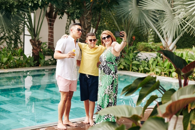 Enthousiaste famille prenant selfie près de la piscine de la station thermale
