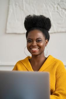 Enthousiaste femme africaine travaillant à distance sur ordinateur portable