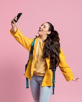 Enthousiaste femme appréciant voyager tout en prenant un selfie