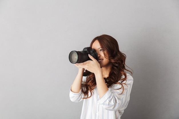Enthousiaste femme asiatique debout isolée, prenant une photo avec appareil photo