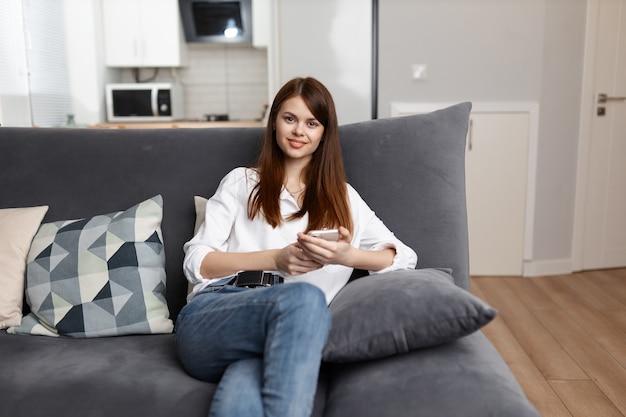 Enthousiaste femme assise sur le canapé avec un téléphone dans ses mains dans un appartement.