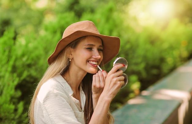 Enthousiaste femme blonde dans un style décontracté portant des vêtements et un chapeau de feutre se maquille avec un crayon à lèvres et se regarde dans le miroir