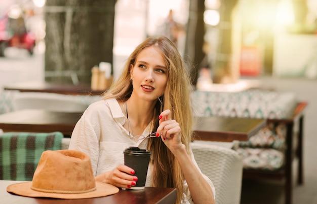 Enthousiaste femme blonde souriante est assise dans un café de la rue et boit du café