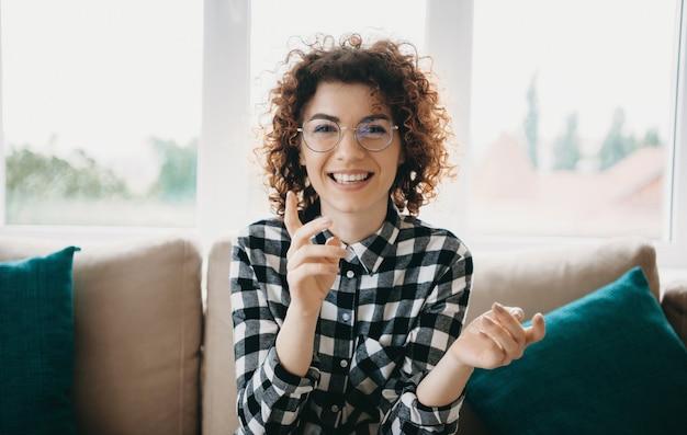Enthousiaste femme caucasienne aux cheveux bouclés et lunettes souriant à la caméra alors qu'il était assis près de la fenêtre sur le canapé