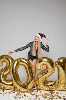 Enthousiaste femme caucasienne aux longs cheveux blonds célèbre la nouvelle année 2021 avec beaucoup de confettis dorés et une coupe de champagne