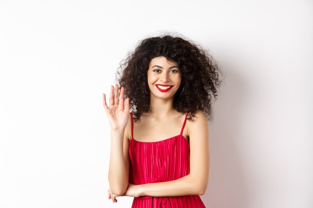 Enthousiaste femme élégante disant bonjour, agitant la main et souriant à la caméra, saluant quelqu'un, debout en robe rouge sur fond blanc.
