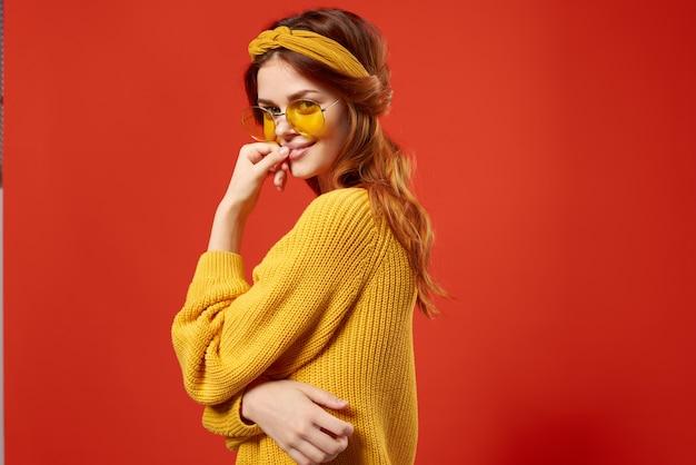 Enthousiaste femme hippie chandail jaune lunettes émotions rouges.